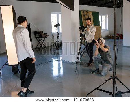 Professional photo and video production team work together. Two photographers taking shots of male model in studio. Fashion photoshooting backstage
