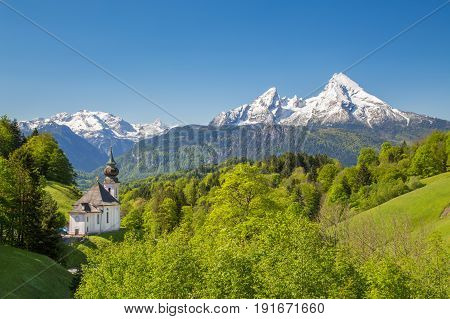 Classic view of Maria Gern pilgrimage church embedded in idyllic scenery with famous Watzmann mountain top in the background on a beautiful sunny day with blue sky in springtime Bavaria Germany