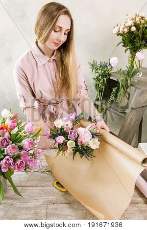 Woman packing pink spring bouquet top view. Young florist make floristry assemble in workshop on wooden background