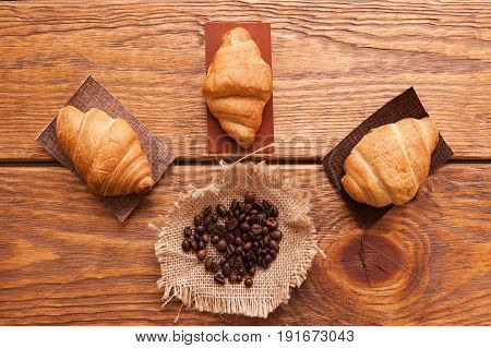 Roasted coffee beans and variety of desserts on wooden background. Closeup of seeds on dark brown cafe table. Top view.
