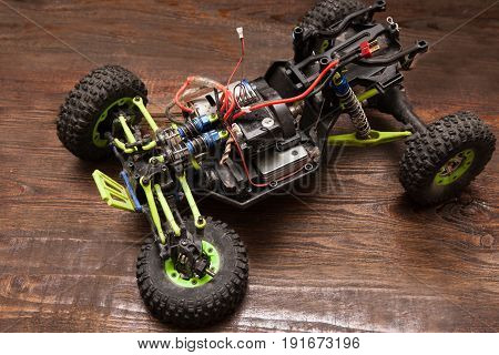 Rc radio control car crawler model toy without wheel on wooden background. Green toy suv on table, free space