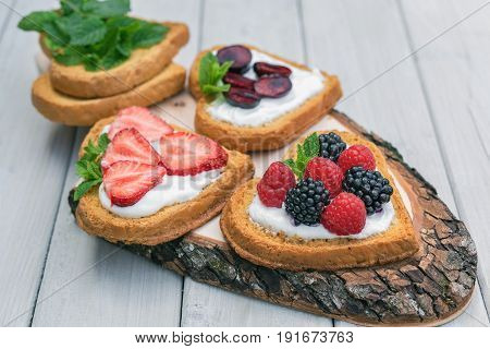 Heart shaped biscuits spread with quark strawberries blackberries raspberries cherries and a twig of mint presented on a tree disk