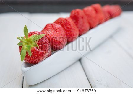 Olive boat filled with strawberries on a wooden table
