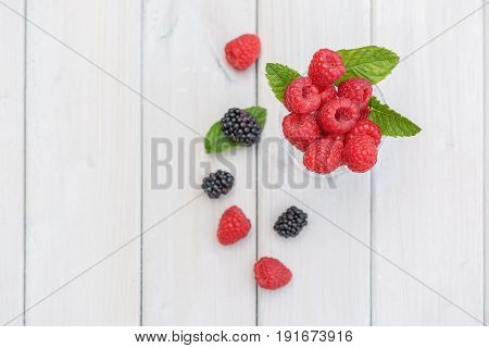 Jam glass filled with raspberries and a twig mint decorated with loose blackberries on the table top