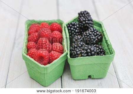 Raspberries and blackberries in a separate cardboard box on a white wooden board