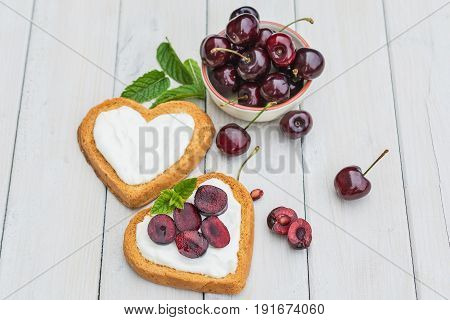 Bowl filled with cherries and heart shaped biscuits spread with quark cherries and a twig of mint