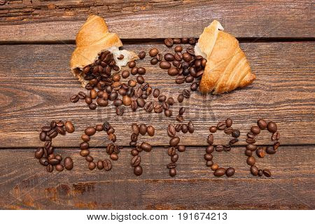 Roasted coffee beans in croissant on wooden background. Closeup of seed filling on dark brown table. Top view. Extra energy concept