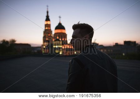 The believer goes to the Christian church. Silhouette of a young man against the background of the night sky and a shining place of worship