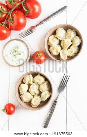 Top view: two portions of meat dumplings ravioli with meat on white wooden background
