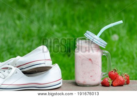 Sneakers, Mug Of Yogurt And Strawberry On A Background Of Green Grass, Copy Space