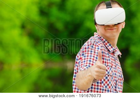 Man in a helmet of virtual reality against the background of nature.Thumbs up
