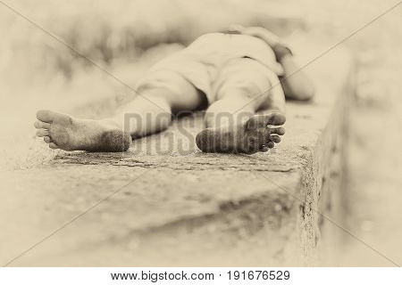 Warm evening. The man is sleeping on a concrete bench. Dirty heels. Monochrome image sepia. Soft focus