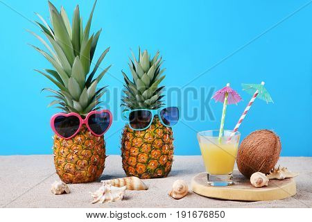 Pineapples With Sunglasses And Glass Of Juice On Beach Sand