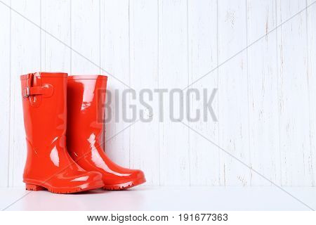 Red Rubber Boots On Wall Paneling Background