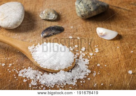 Close up of sea salt in wooden spoon over wood background