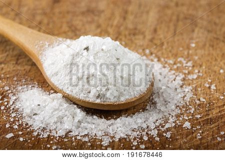 Coarse grained sea salt on wooden background