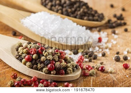 Wooden spoons with sea salt and peppercorns on wooden background. Macro with shallow dof.