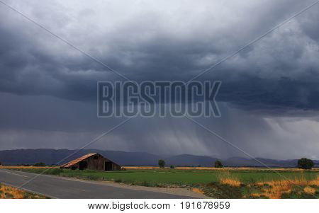 Isolated barn in field under storm cloud with rain falling int he distance.