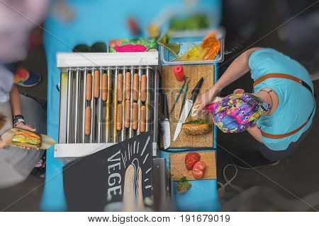 High angle view of cooking barbecue. Sale and service. Man with healthy vegan street food, sausages, made with soy protein wiener on vegan hot dog bun, vegetables, selective focus. Summer healthy vegan grill concept
