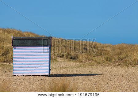 Striped beach hut on sandy beach. Secluded beach vacation. Pink and blue wooden shack. Blue sky background with copy space.