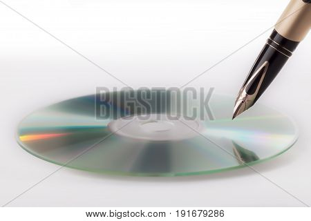 Writing music. Dream song. Soft image of a fountain pen and blank CD. Against white background with copy space.