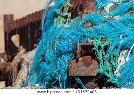 Dangerous plastic sea pollution. Tangled nylon fishing net washed up and caught on a rusty beach groyne.