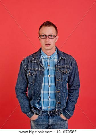 man in nerd glasses shirt and jeans jacket on red background with hands in pocket denim style beauty and fashion student lifestyle