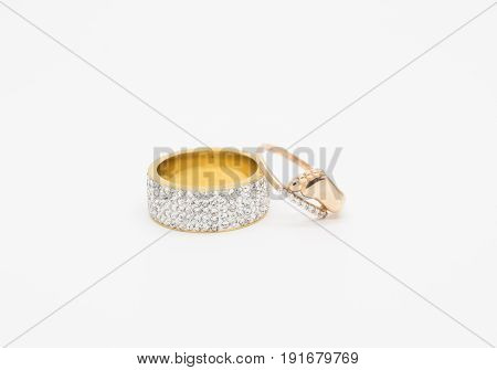 One thick gold ring embedded with cubic Zirconia in five rows and one gold ring with diamonds for wedding and child birth