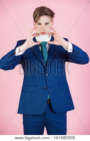 man hold credit or business card young businessman in blue classy outfit on pink background formal fashion and success saving and banking business etiquette and ethics copy space