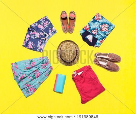 Collection of bright summer clothes on yellow background. Beautiful clothes decomposed in a circle.