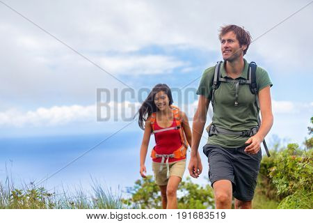 Hiking people hikers couple on nature trek walking on summer hike in mountains. Man trekking with woman, Healthy lifestyle travel vacation.