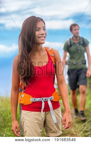 Happy woman hiker hiking couple in nature on hike trail on summer travel vacations. Healthy lifestyle young Asian girl smiling enjoying walk with man.
