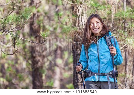 Happy hiker girl hiking in forest nature on hike trail in autumn outdoors travel vacations. Healthy lifestyle young Asian woman smiling portrait with poles, jacket, backpack.