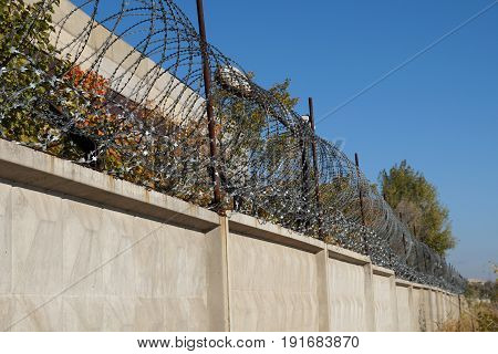 Barbed wire on the concrete fence protecting the industrial enterprise