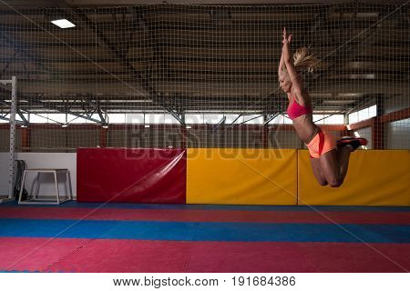 Athlete Performing A Long Jump In Gym