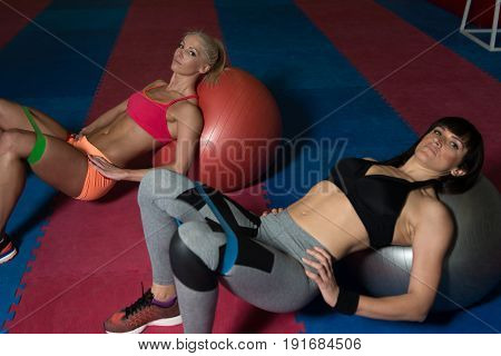 Couple Exercise Together With Resistance Bands On Ball