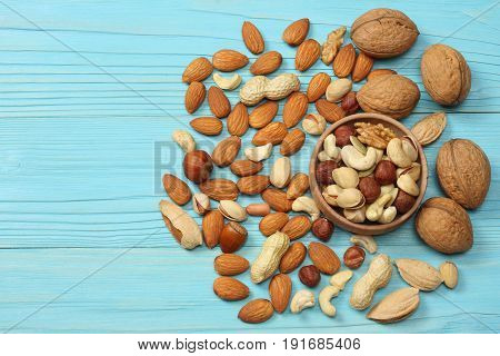 mix almonds, cashew nuts, hazelnut, peanuts, walnuts, pistachio on wooden background. Top view with copy space