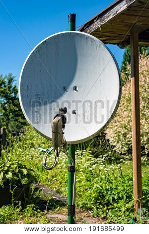 A Old satellite dish standing in a garden in Tuhringia