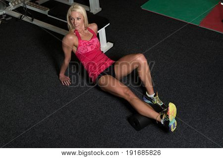 Athletic Woman Stretches With Roller In Gym