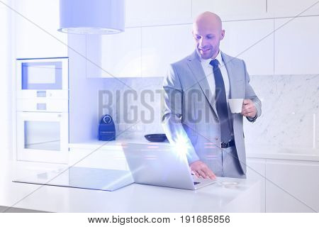 Mid adult businessman having coffee while using laptop in kitchen