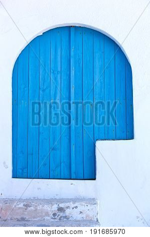 intense blue wooden door in a white wall mediterranean colors