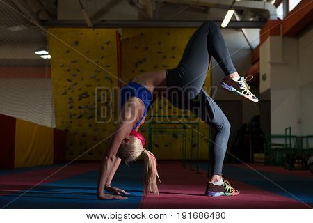 Athletic Woman Stretches In Gym