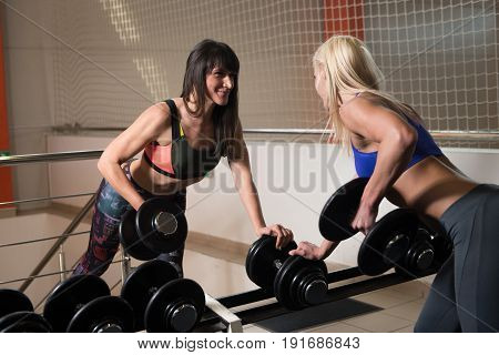 Fitness Couple Doing Exercise For Back With Dumbbells