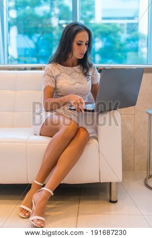 Young woman sitting on sofa at hotel lobby working on laptop computer.
