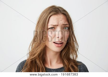 Portrait of young beautiful girl looking at camera suspiciously with opened mouth over white background. Copy space.