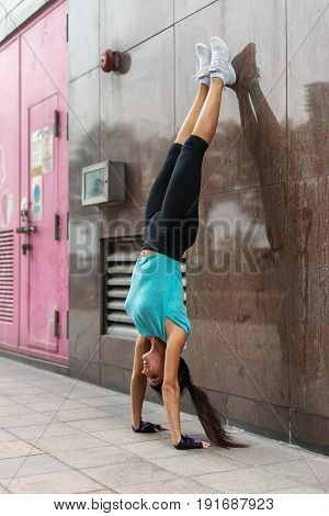 Young woman doing handstand exercise against the wall on the city street