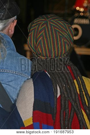reggae style woman with dreadlocks and reggae cap rear view at a music event
