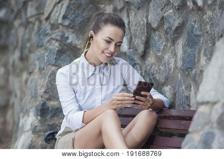 Youth Lifestyle Concepts and Ideas. Smiling Caucasian Brunette Woman With Headphones Relaxing on Bench and Chatting on Cellphone Outdoors. Horizontal Image
