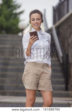 Youth Lifestyle Concepts and Ideas. Stylish Modern Caucasian Brunette Woman Posing Outdoors With Smartphone Gadget and Wearing Wireless Headphones. Vertical Image