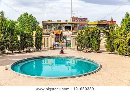 Yazd, Iran - MAY 5, 2015: Tourist photographing the fire temple Atash Behram by the pool.
